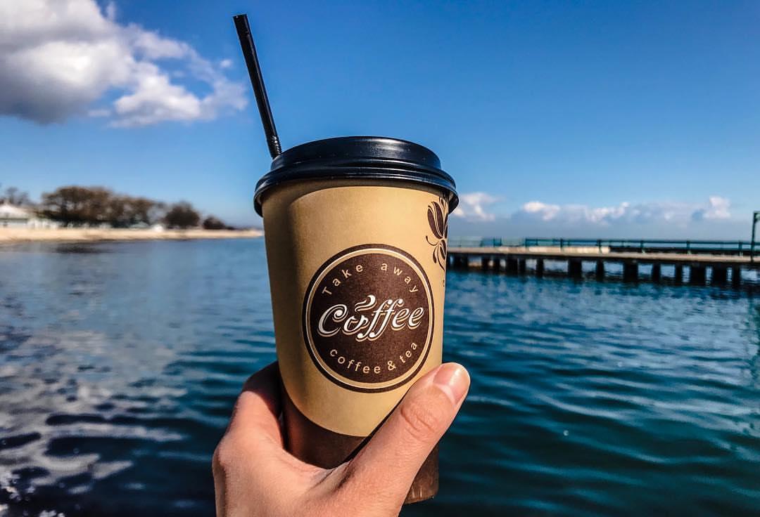 Стакан кофе на фоне моря